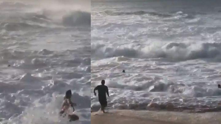VIDEO: Fuerte ola arrastra a bañista a las profundidades y surfista la rescata