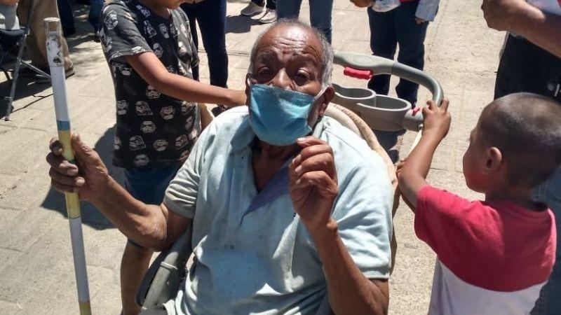 """VIDEO: """"Vivimos solos con mi abuelo""""; niños lo llevan en carriola al centro de vacunación"""